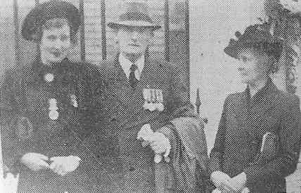 Mr. and Mrs. Watts and their daughter, with medals